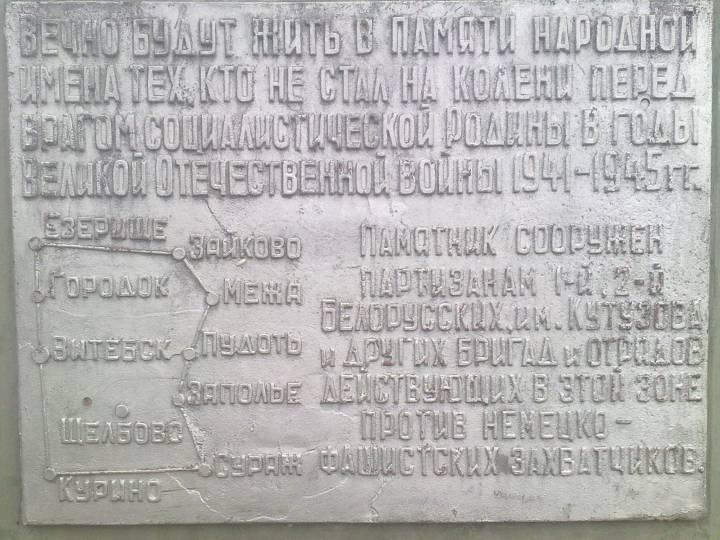 Знак у памятника Партизану в деревне Щелбово,около озера Тиосто. Координаты памятника Широта 55.56444 С Долгота 30.50117 B