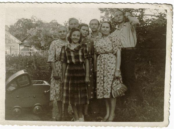 5. Janina Bublewicz stoi w samym środku w ciemnej sukience w kwiaty. Zdjęcie zrobione w miejscu jak na foto nr. 2.